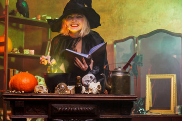 Portrait of smiling witch in black hat reading spell over pot with green steam