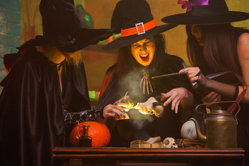 Portrait of three witches in hats cooking poison in cauldron