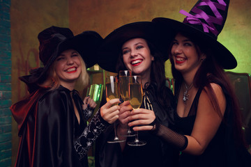 Image of three young witches with glass of champagne
