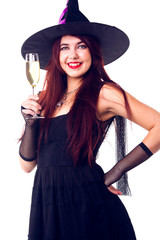 Portrait of witch brunette with wine glass with wine in black dress