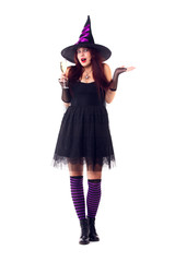 Full-length image of surprised witch with wine glass with wine in black dress and hat