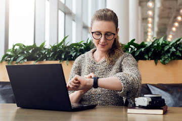 Portrait of young businesswoman sitting in cafe,working on laptop,looks at wrist watch. Online marketing, education.