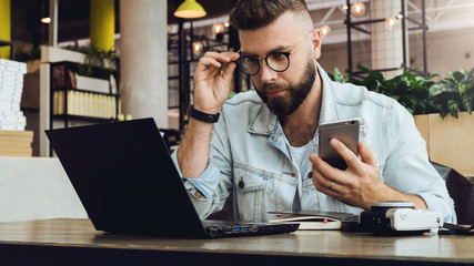 Hipster man sits in cafe, uses smartphone, works on laptop. Businessman reads information message on computer screen.