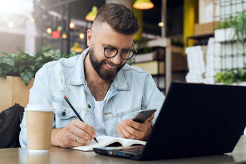 Bearded hipster man sits at table in front of laptop and writes in notebook,student prepares for exams,freelancer works.