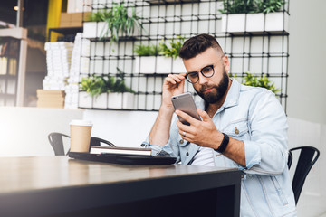 Young bearded businessman is sitting in cafe,using smartphone.On table is closed laptop,cup of coffee.Freelancer work.