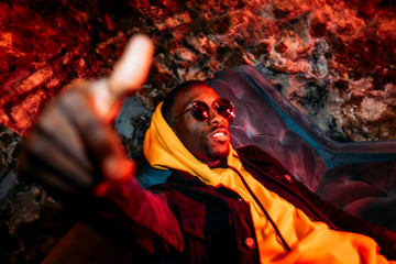 African man rapper among colorful light. Long exposure