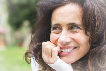 Lovely middle aged woman with playful look bites her nails with smile on blur background. Pretty mature lady with optimistic expression