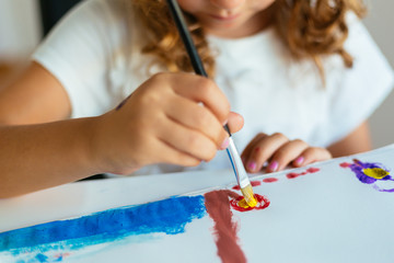 Close up of litte girl holding paintbrush and painting on paper at living room