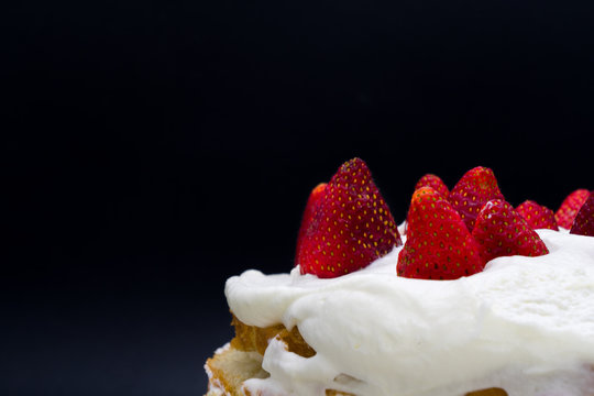 Organic strawberry cake with whipped cream isolated on a black background