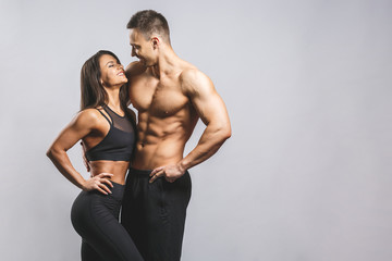 Obraz Athletic man and woman isolated over white background. Personal fitness instructor. Personal training. - fototapety do salonu