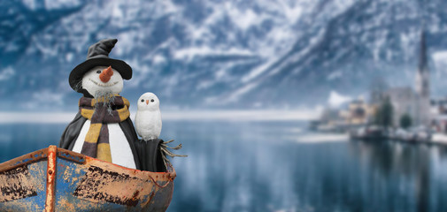 merry christmas a snowman with a white owl sailing on the lake of a cold winter mountain landscape scene