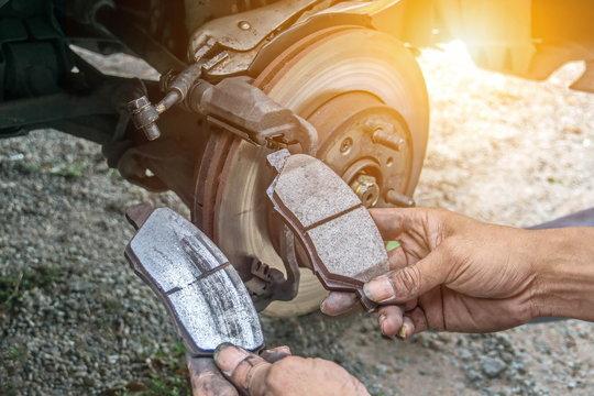 Guys are repairing cars.The car is repairing the brake system.
