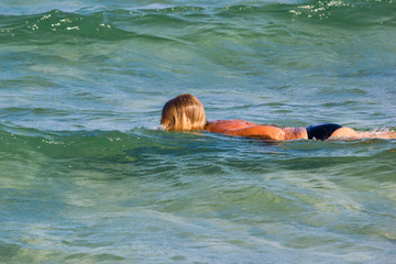 Girl swimming on the sea waves in the rays of summer sun