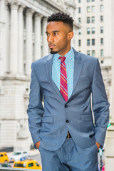 Portrait of Young African American Businessman with beard in New York, wearing dark sky blue suit, white patterned shirt, violet red patterned tie, standing on street by office building, looking away