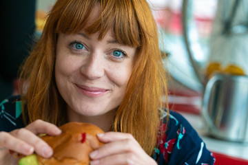 Portrait of ginger girl with blue eyes on a floral dress in diner eating a burger and smiling