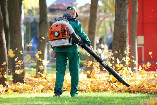 worker in the Park cleans the grass from fallen leaves with the help of a wind turbine