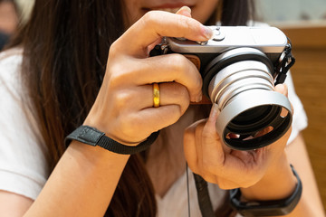 Beutiful women gripping mirrorless camera for shot food or view picture.