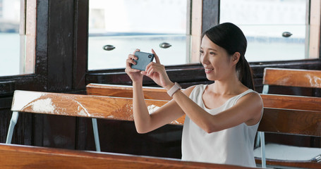 Woman taking photo on cellphone on ferry