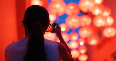 Woman taking photo of the red chinese lantern