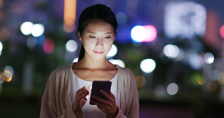Wall Mural - Woman send sms on cellphone in city at night