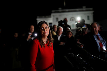 U.S. White House Press Secretary Huckabee talks with journalist outside of the White House in Washington