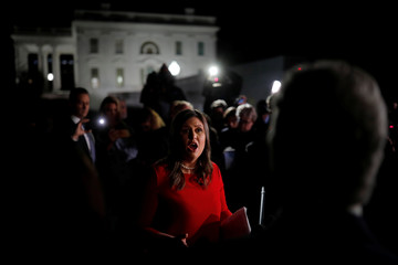 U.S. White House Press Secretary Sanders talks with journalist outside of the White House in Washington