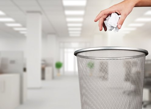 Hand throwing out paper into trash basket isolated
