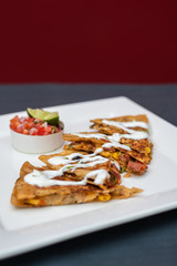 Spanish or Mexican dish Quesadilla served with salad and sauce
