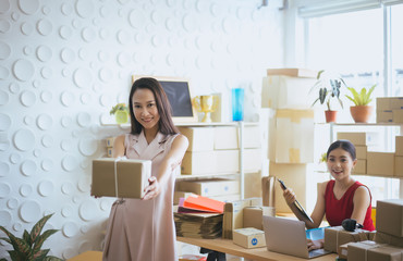 Happy asian business woman owner holding parcel and working together,Female smiling start up entrepreneur SME online at home office