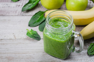 Organic Healhty Vegetarian Food. Fresh homemade raw vegetable and fruit green smoothie in mason jar with apple, banana and spinach leaves on shabby wooden background. Copy space