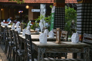 Empty wooden restaurants chairs and tables in the garden, evening time before dinner, no people
