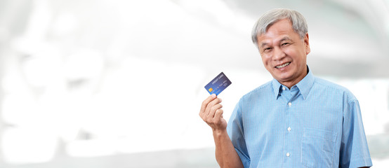 Portrait of happy senior asian man holding credit card and showing on hand smiling and looking at camera on isolated blurred background banner feeling positive and enjoy. Older male lifestyle concept.