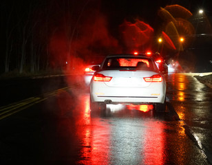 car driving in the rain at night in the street