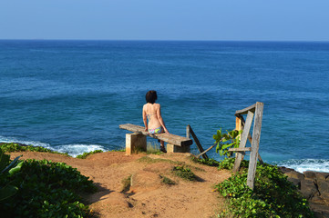 the girl looks at the Indian ocean on the beach of the island of Ceylon