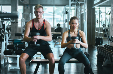 Sporty couple man and woman exercise with dumbbells or does the exercises at gym