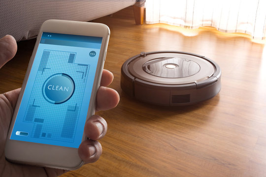 Hand holding smartphone with application control robot vacuum cleaner on screen mobile phone.Smart life technology concepts