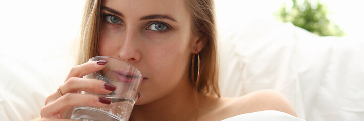 blond woman hold glass of water in arm early morning stay in bed
