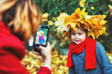 mom takes pictures of her daughter with a mobile phone in the autumn Park