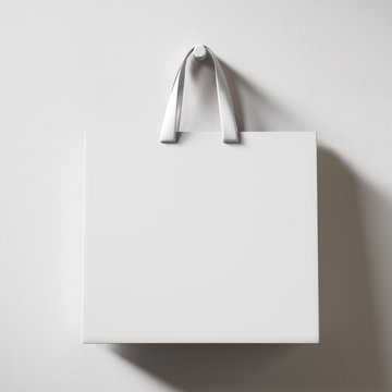 Hanging white shopping bag isolated on bright background. 3d rendering mock up