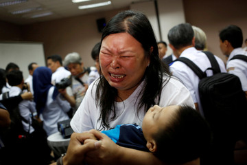 Woman, whose husband was on Lion Air flight JT610, cries as she holds their son in Jakarta