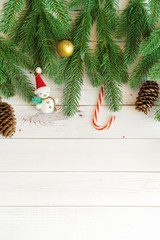 Green Fir tree branches and christmas accessories on light wooden background.