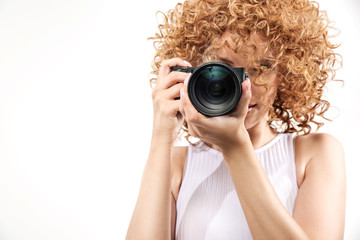 Attractive frizzy-haired lady taking a photograph