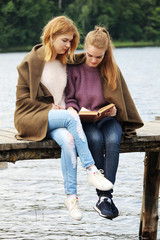 Two young girls read a book together