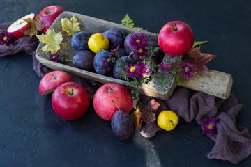 on a dark table autumn harvest: red apples, plums, autumn flowers