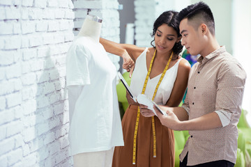 Creative fashion designers standing near the model of shirt and choosing color on digital tablet in a modern studio