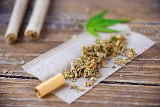 Cannabis joints with rolling paper over wood background