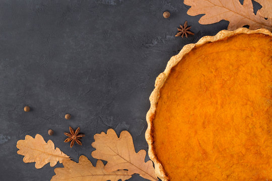 Frame from orange pumpkin pie, anise star, pepper and oak autumn leaves on a concrete dark gray background. Thanksgiving Day, culinary, recipe, menu concept. Top view, flat lay, copy space, mock up