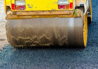 Closeup compact steamroller flatten out the asphalt.