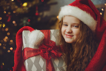 Beautiful little girl with gift and in Santa hat.