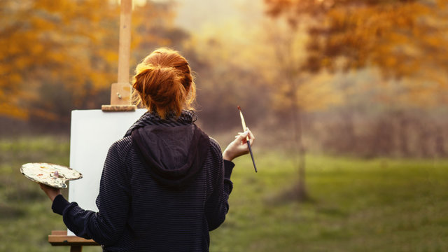 girl drawing a picture on an easel in nature, young woman with paint brush among autumn trees, a concept of creativity and a hobby